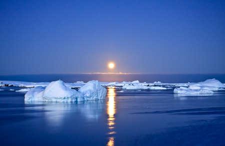 calentamiento global: Noche de verano en Antarctica.Icebergs flotando en la luz de la Luna