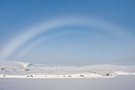 no cloud: rainbow over snow-covered slopes of the Antarctica
