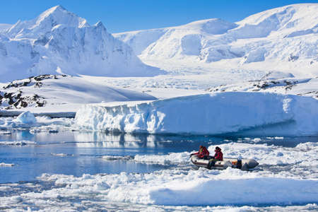 expeditions: two men in the boat in Antarctica