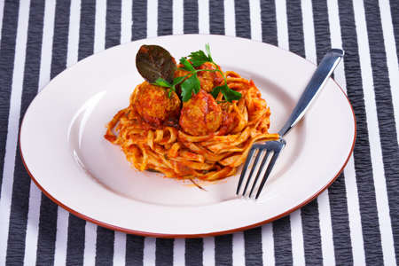Spaghetti with meatballs on a white plate