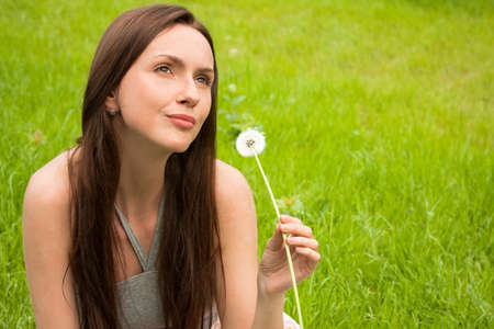 Girl with dandelion on green field photo