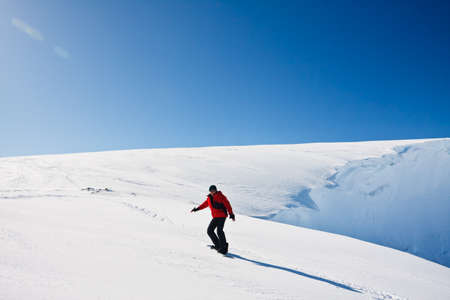 Man moves on snowboard. Glacier in background. Antarctica Stock Photo - 9798388