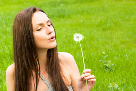 Girl with dandelion on the green field photo