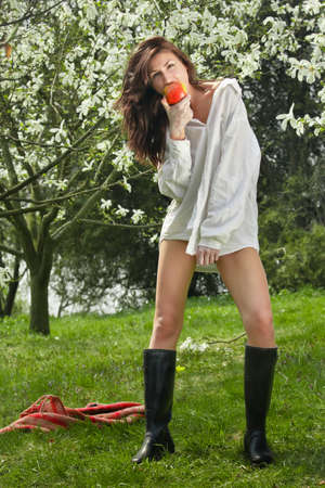 Beautiful young girl eating an apple in the park photo