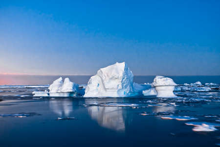 Summer night in Antarctica.Icebergs floating in the moonlight Stock Photo