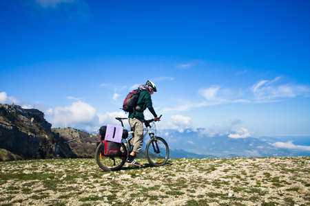 Young man riding a bike over the precipice in the mountains photo