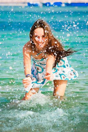summer fun: Beautiful young girl splashing the water in the sea Stock Photo