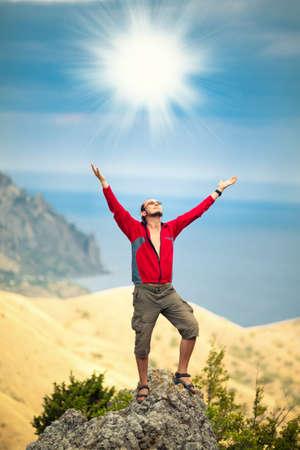L'uomo in cima alla montagna tenendo le braccia in alto