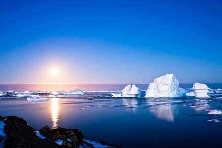 Summer night in Antarctica.Icebergs floating in the moonlight photo