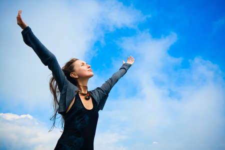 manos levantadas al cielo: Hermosa mujer joven bajo el cielo azul. Retrato