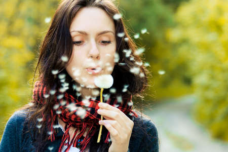 Girl blowing on white dandelion in the forest Stock Photo