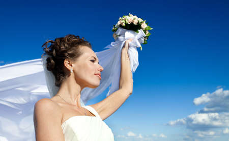 Portrait of a young bride in a white dress with a bouquet of flowers photo
