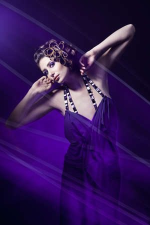 beautiful young woman in evening dress in violet light photo