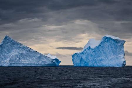 빙산: 남극, 어두운 하늘에서 거대한 빙산 스톡 사진