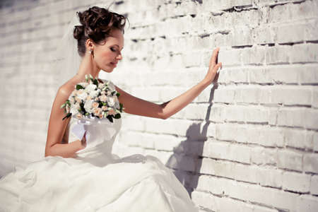Portrait of a young bride in a white dress with a bouquet of flowers Stock Photo