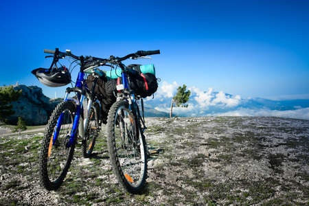 two bikes on the precipice, sky and mountains in the background photo