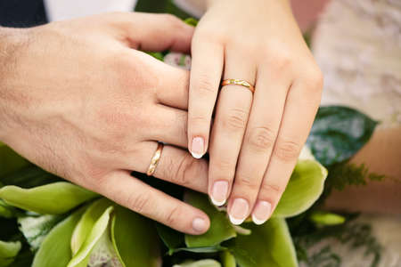 Bride and groom holding hands with wedding rings photo