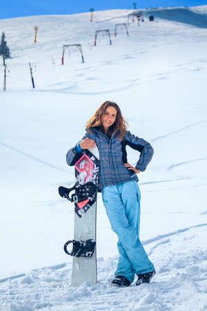 彼女の手でスノーボード冬の服でスノーボーダーの若い女の子