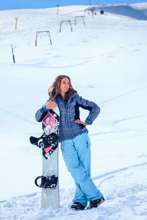young snowboarder girl in winter clothes with snowboard in her hands photo
