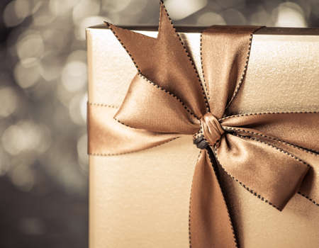 wrapped up: gift box with golden ribbon, glittery gold background