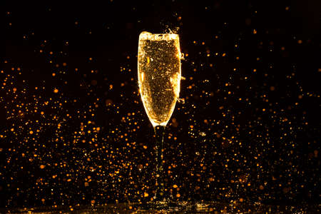Champagne pouring in glass on a black background Stock Photo