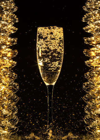 Champagne pouring in glass on a black background photo