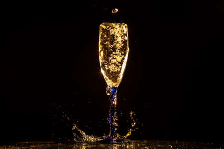 fresh graduate: Champagne pouring in glass on a black background Stock Photo
