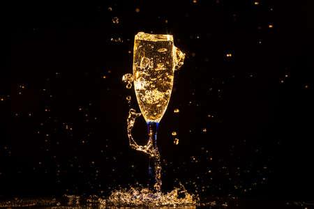brindisi spumante: Champagne versando in vetro su uno sfondo nero