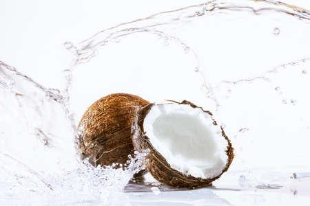 白で隔離され、大きなスプラッシュでひびの入ったココナッツ