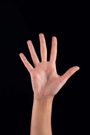 partes del cuerpo humano: Mujer femenina de la mano en el fondo oscuro
