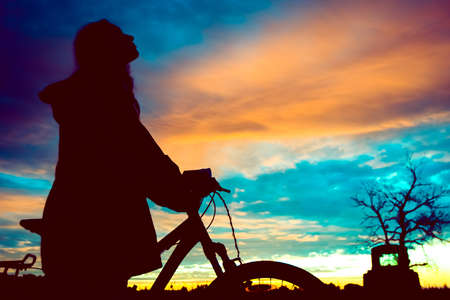 Girl with a bicycle watching the sunset Stock Photo
