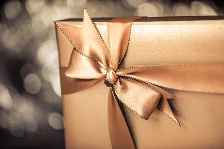 package design: gift box with golden ribbon, glittery gold  Stock Photo