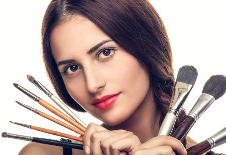 Beautiful woman with makeup brushes near her face - isolated on white photo