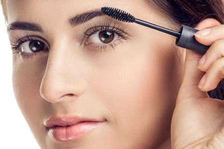 Woman applying mascara on her long eyelashes photo