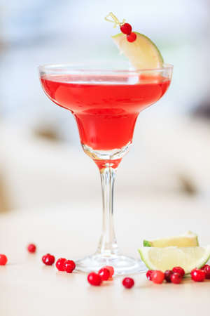 cosmopolitan cocktail garnished with a lime and berries photo
