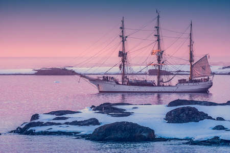 galley: sailing ship in Antarctica at dawn among the icebergs