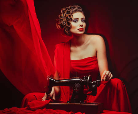 beautiful young pinup woman with sewing machine in red material photo