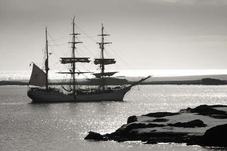 Sailing ship at dawn among the icebergs in Antarctica Stock Photo