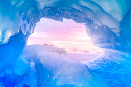 blue ice cave covered with snow and flooded with light Imagens
