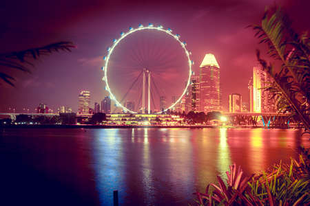 water wheel: Singapore city skyline at night Editorial