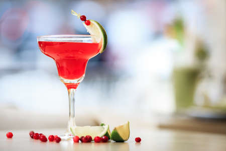 cosmopolitan cocktail garnished with a lime and berries