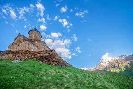 mediaeval: Holy Trinity Church near Mount Kazbek in Georgia. Tsminda Sameba. Mediaeval Church in mountains