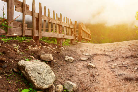 dirt ground: Dirt ground road with rocks and wooden fence in the misty mountains
