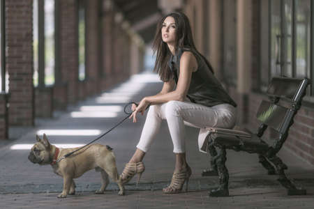 Young beautiful brunette woman sitting with dog on retro bench