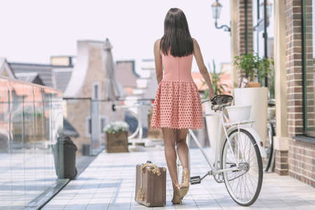 beautiful brunette woman in pink dress with bicycle and suitcase