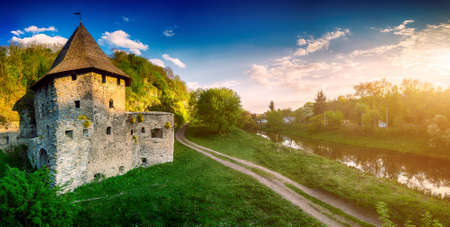 standing stone: Ancient stone castle in Kamianets Podilskyi standing on hill with green trees and bushes with rural road and river