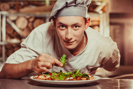 young male cook preparing delicious appetizer with herbs on white plate