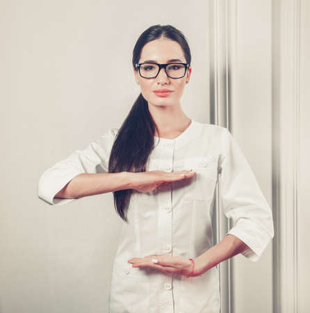 Attractive female expert beautician. Beautiful Young woman in glasses and healthcare worker uniform