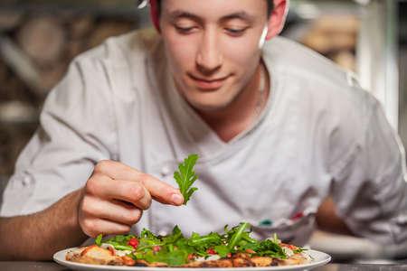 chef italiano: macho joven cocinero preparar delicioso aperitivo con las hierbas en la placa blanca Foto de archivo