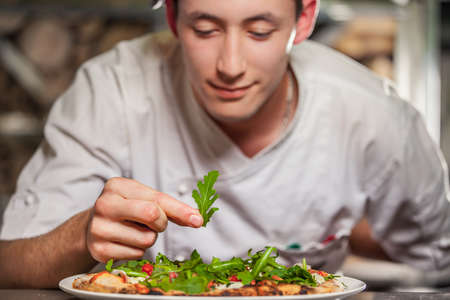meal preparation: young male cook preparing delicious appetizer with herbs on white plate